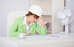 Tired woman engineer in workplace Stock Images