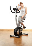 Tired woman exercising on bicycle Stock Images