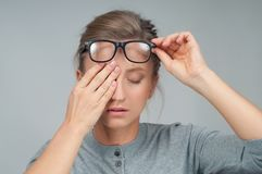 Tired woman in eyeglasses, covering eyes with hands. Tired woman in eyeglasses with eyes pain, covering eyes with hands stock images