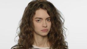 Tired woman face on white background. Depressed face expression. Tired woman face on white background. Portrait of upset woman waving head no in studio. Negative stock footage