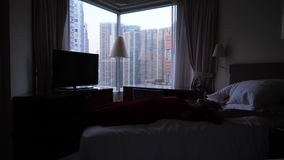 Woman fall on bed and relax. Tired woman fall on bed to relax. Hong Kong city panorama out of window stock footage
