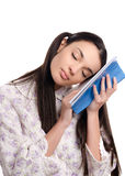 Tired woman falling asleep reading. Beautiful girl in pajamas falling asleep with a book in her hands. Isolated on white background stock images