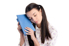 Tired woman falling asleep reading. Beautiful girl in pajamas falling asleep with a book in her hands. Isolated on white background royalty free stock photos