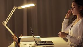Tired woman in glasses with laptop at night office stock footage