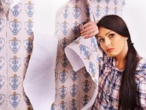 Tired woman glues wallpaper . Royalty Free Stock Photography