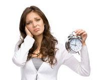 Tired woman handing alarm clock Royalty Free Stock Image