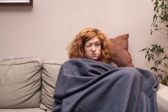 Tired woman having a cold and resting on sofa Stock Photography