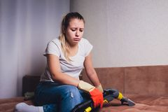 Tired woman having rest after cleaning home, lying on sofa in the living-room, copy space. Housekeeping and home stock photography