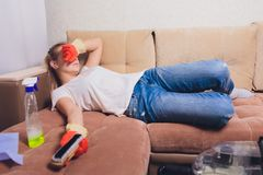 Tired woman having rest after cleaning home, lying on sofa in the living-room, copy space. Housekeeping and home royalty free stock image