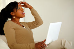 Tired woman with headache browsing the Internet. Portrait of a tired woman with headache browsing the Internet on her laptop at home indoor Royalty Free Stock Image