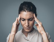 Tired woman with headache. Young pensive woman feeling depressed and having a bad headache, she is touching her temples stock images