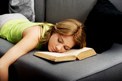 Tired woman with her head on book. Royalty Free Stock Photography