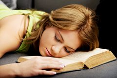 Tired woman with her head on book. Royalty Free Stock Image