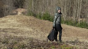 Tired woman hiker walking down to the hill stock video footage