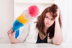 Tired woman holding a brush to dust Royalty Free Stock Images