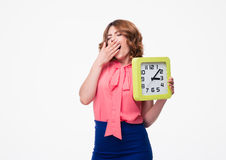 Tired woman holding clock Stock Images