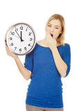 Tired woman holding a clock. Stock Photos