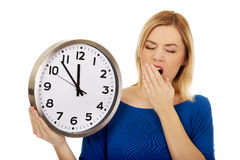 Tired woman holding a clock. Royalty Free Stock Image