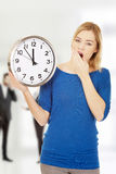 Tired woman holding a clock. Stock Image