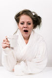 Tired woman holding coffee cup in her hand. And wearing a white robe wearing Stock Photos