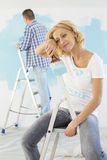 Tired woman holding paintbrush with man painting in background Royalty Free Stock Image