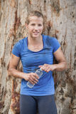 Tired woman holding water bottle during obstacle course. In boot camp royalty free stock image