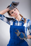 Tired woman holding wrench. On isolated background Stock Photography