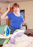 Tired woman irons clothes Royalty Free Stock Photography