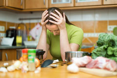 Tired woman at kitchen Stock Photos