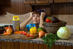 Tired woman in kitchen among vegetables.  Stock Image