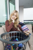 Tired woman with laundry basket sitting on sofa at home Stock Photo