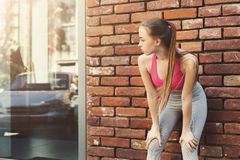 Tired woman leaning on brick wall. Relaxing from jog training, copy space Royalty Free Stock Photo