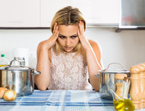 Tired woman leaning her elbows at the kitchen Royalty Free Stock Photography