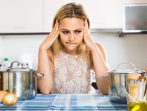 Tired woman leaning her elbows at the kitchen Royalty Free Stock Photos