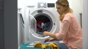 Tired woman loading clothes in washing machine, annoyed with housework routine stock video footage