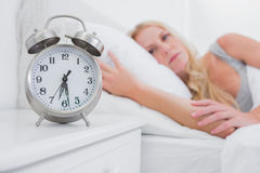 Tired woman looking at the alarm clock Royalty Free Stock Photos