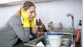 Upset tired woman looking at big heap of dirty kitchens in kitchen sink. Tired woman looking at big heap of dirty kitchens in kitchen sink Stock Images
