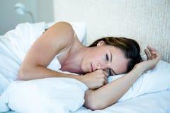 Tired woman lying awake in her bed Stock Image