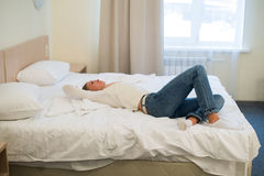 Tired woman is lying in bed with her arm on head and eyes. Young woman with long hair, wears jeans.  Stock Photos