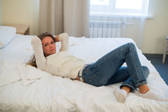 Tired woman is lying in bed with her arm on head and eyes. Young woman with long hair, wears jeans.  Stock Photo