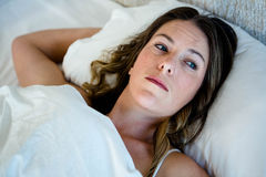 Tired woman lying in bed staring into space Royalty Free Stock Images