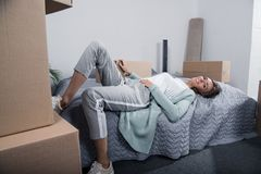Tired woman lying on bed after unpacking cardboard boxes at new home, moving. Home concept Stock Photo