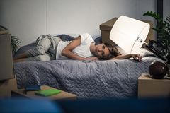 Tired woman lying on bed after unpacking cardboard boxes at new home, moving. Home concept Stock Photos