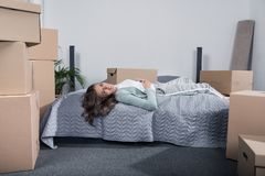 Tired woman lying on bed after unpacking cardboard boxes at new home, moving. Home concept Royalty Free Stock Photos