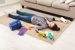Tired woman lying on carpet after cleaning home. In the living-room, copy space. Housekeeping and home cleaning concept stock images
