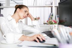 Tired woman manager in the office. After a hard day`s work Stock Photos