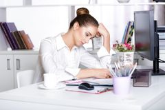 Tired woman manager in the office. After a hard day`s work Stock Image