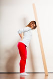 Tired woman moving into apartment carrying box. Royalty Free Stock Photography