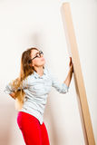 Tired woman moving into apartment carrying box. Royalty Free Stock Photo