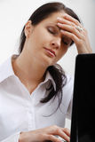 Tired woman near laptop. Tired woman is in front of a laptop. She is closed her eyes. She clasps her hand to her forehead Stock Photography
